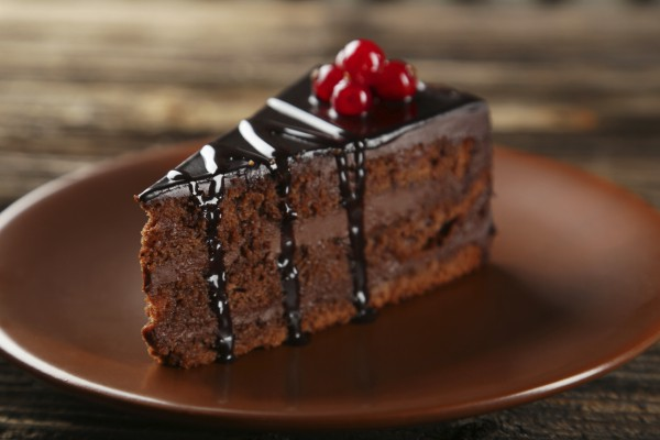 Dark chocolate cake on brown wooden background