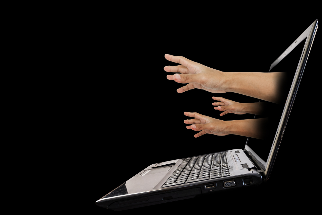 Hand reach out from laptop screen, isolated on black background